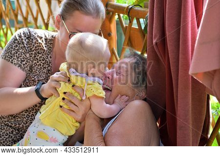 The Grandmother To Snuggle From Joy To The Newborn In The Background With Her Mother