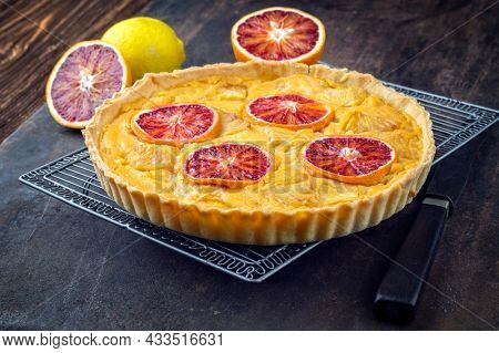 Traditional French tart au citron with blood orange slices served as close-up in a backing form