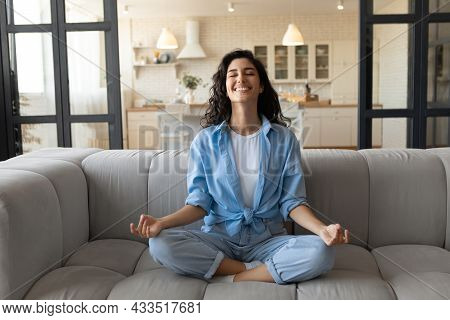 Cheerful Young Lady Sitting On Comfy Couch, Meditating With Closed Eyes At Home, Full Length
