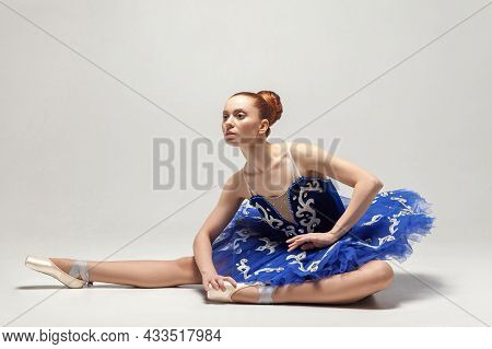 Attractive Ballerina With Bun Collected Hair Wearing Blue Dress And Pointe Shoes Sitting On White St