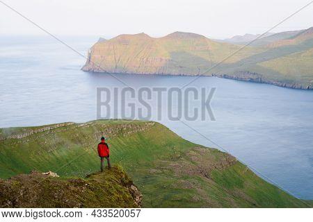 Tourist enjoying the view of Vagar Island from Mount Sornfelli on Streymoy island in the Faroe Islands
