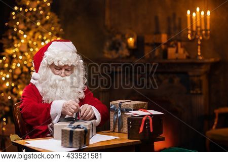 Workplace of Santa Claus. Cheerful Santa is wrapping the gift while sitting at the table. Fireplace and Christmas Tree in the background. Christmas concept.