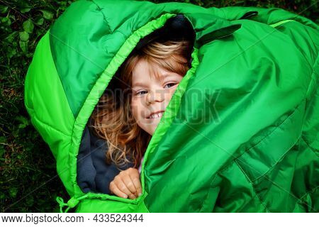 Preschool Little Girl In Sleeping Bag Camping. Outdoors Activity With Children In Summer. Fun And Ad