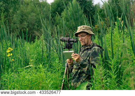 Man Birdwatcher Looks At Or Writes Down Information On The Tablet While Standing Among The Tall Gras