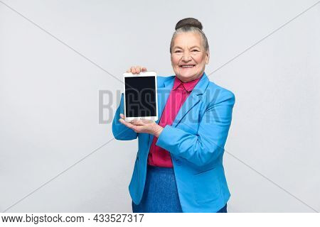 Aged Woman Holding And Showing Tablet Screen With Toothy Smiling And Satisfied Face. Grandmother In
