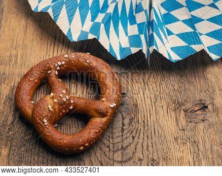Tasty Pretzel With Bavarian Flag On A Rustic Wooden Table, Oktoberfest Or Traditional Bavarian Food