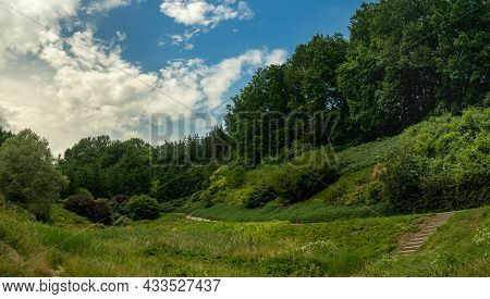 Summer Time Day Green Park Hills Landscaped View With Meadow And Trees Area