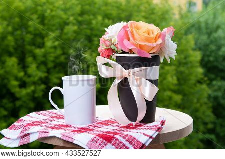 Bouquet Of Rose Flowers And Coffee Mug With Steam On Wooden Table At Balcony. Green Background.