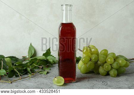 Bottle Of Vinegar, Grape And Leaves On Gray Textured Table