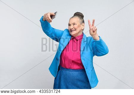 Aged Woman Making Selfie With Peace Sing And Smilling. Portrait Of Handsome Expressive Grandmother I