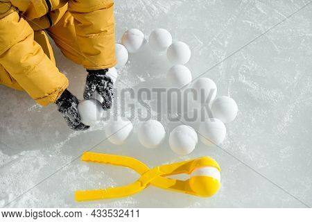 A Child In A Yellow Jumpsuit Lays Out Heart-shaped Snowballs On The Ice, Made With A Tool Similar To