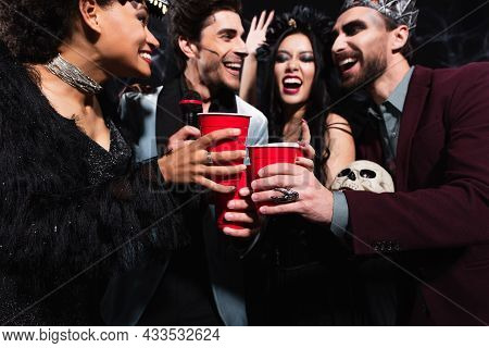 Cheerful Multiethnic Friends Toasting With Plastic Cups While Singing Karaoke On Black
