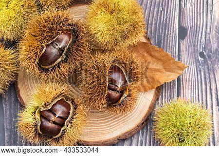 Ripe Chestnuts On A Wooden Background Close Up. Sweet Raw Chestnuts. Chestnuts With Skin. Organic Fo