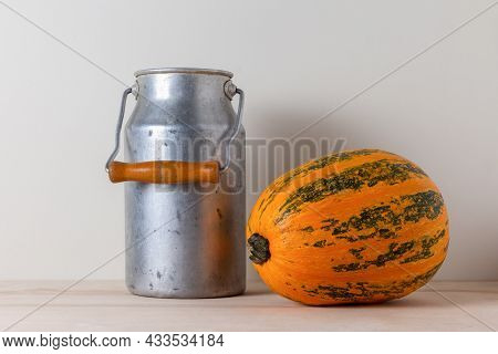 Old Aluminum Milk Can With Wooden Handle And Ripe Yellow Pumpkin On A Kitchen Table Against A Light