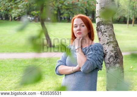 Attractive Young Woman With Red Hair In A Blue Knitted Sweater Stands By A Birch Tree And Looks Pens