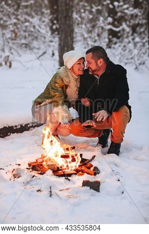Joyful Happy Family Couple In Love Basking By Campfire Outside In Winter Snowy Forest, Man And Woman