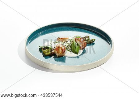 Luxury dish - grilled scallops with asparagus and creamy espuma. Roasted scallop with cream sauce and asparagus on white background. Delicacy seafood in restaurant menu -  sea scallop