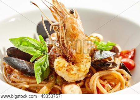 Italian dish - seafood linguine isolated on white background. Pasta with prawn, mussels, octopus,  squid in tomatoes marinara sauce. Seafood pasta in Italian restaurant menu. Seafood on white plate