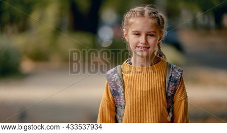 Preteen school girl with backpack looking at camera. Pretty pupil female kid portrait outdoors after education class in autumn park