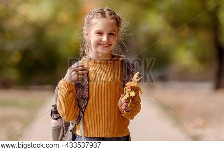 Preteen school girl with backpack holding yellow leaves in her hand, looking at camera and smiling. Pretty pupil female kid after education class at autumn