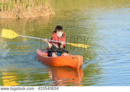 Closeup Of 8 Years Old Brazilian Child Sailing By Kayak In A Small River On A Sunny Day.