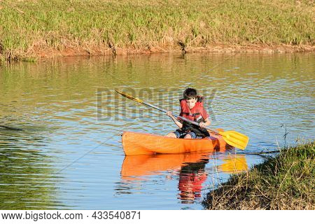 8 Year Old Brazilian Child Sailing In A Kayak In A Small River On A Sunny Day.