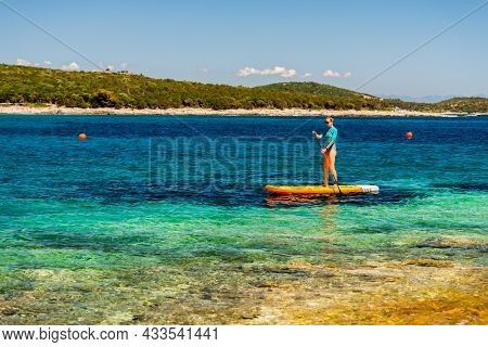 Young Girl Sup Board With A Paddle In Hand - Front View - The Calm Surface Of The Turquoise Sea - Co
