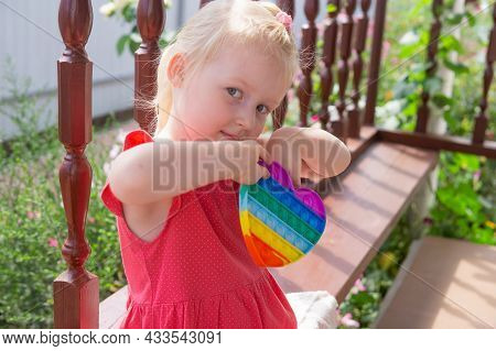 Cute Caucasian Fair Hair Girl In Pink Dress Is Playing And Showing Funny Trendy Silicone Antistress