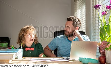 Homeschooling And Elearning. Back To School. Father And Son Use Modern Technology At Home