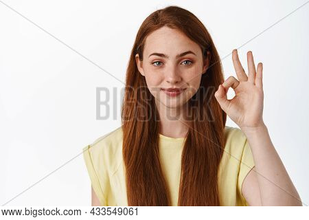Portrait Of Smiling Redhead Woman Looks Confident, Shows Okay Zero Sign, No Proble Gesture, Assure Y