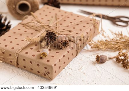 Handmade Gift Box In Craft Packaging And Dry Poppy Flowers On White Desk. Floristic, Herbarium Craft
