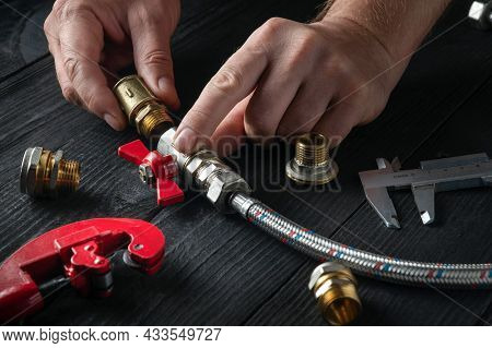 Plumber Connects Brass Fittings To Plumbing Hose. Close-up Of Hand Of The Master During Work In Work