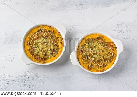 Homemade Pumpkin Casserole Or Gratin With Cheese And Pumpkin Seeds In Two Ceramic Tins On A Light Gr