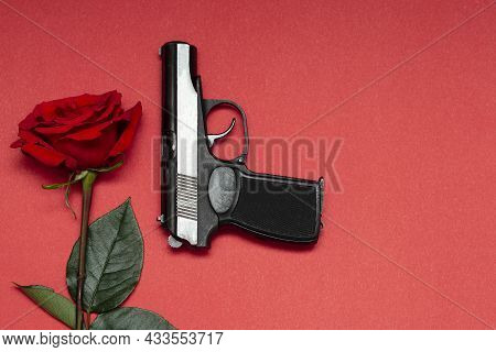 One Red Rose On A Pink Background Next To A Black Gangster Gun. The Concept Of The Mafia Table.