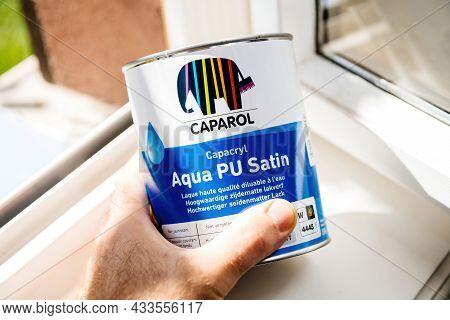 Paris, France - Sep 8, 2021: Pov Male Hand Hear Window Of New Unopened Metal Can With Caparol Aqua P