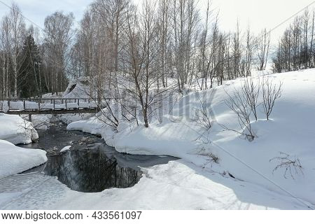 snowy wooden bridge over small river in Siberia