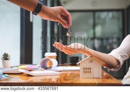 Estate Agent Giving House Keys To New Property Owners After Signing Rental Lease Contract Or Sale Pu