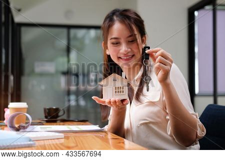 Woman Holding House Model And House Key In Hand. Real Estate And Mortgage Investment Concept.