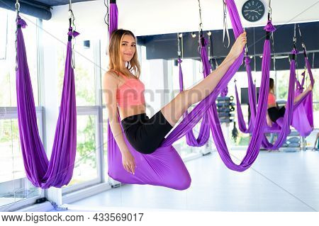 Young Beautiful Woman Practice In Aero Stretching Swing Hanging Upside Down. Aerial Flying Yoga Exer