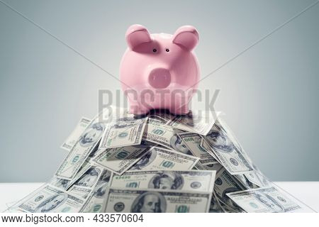 Piggy bank on pile of money concept for business finance, investment, saving or retirement fund