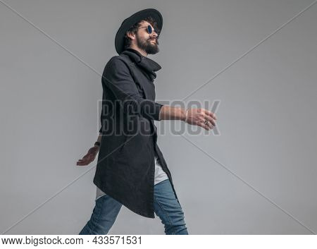 side view of a handsome casual man walking with attitude and wearing sunglasses on gray background