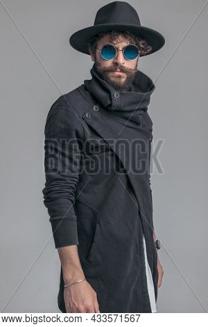 sexy casual man posing with cool attitude and wearing a hat, sunglasses and cardigan on gray background