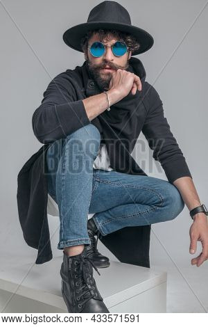fashion guy posing in a squatting position with attitude and wearing cool sunglasses on gray background