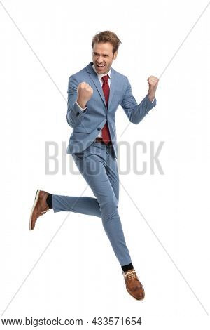 enthusiastic young guy in blue suit holding fists up, laughing and celebrating victory while jumping up in the air on white background in studio