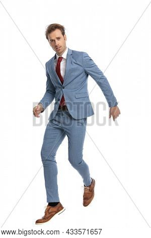 attractive young man in blue suit holding arms in fashion pose while jumping in the air and posing in front of white background in studio, full body