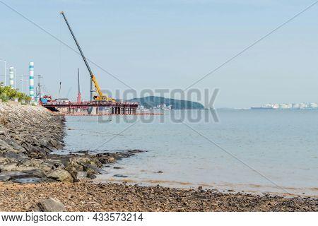 Construction Crane On Platform At Edge Of Seacoast On Overcast Day.