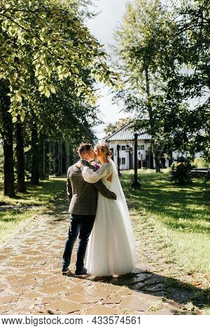 Wedding Day. Beautiful Young Couple Hugs On Ranch, Groom Kisses Bride In White Dress With Veil, Kiss