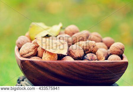 Walnut kernels in a wooden bowl on green background