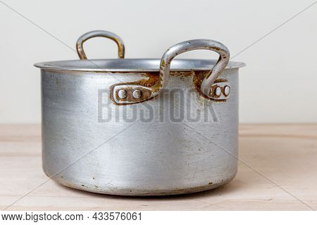An Old Rough Aluminum Saucepan On A Wooden Kitchen Shelf. Used Dishes With Scratches And Marks From