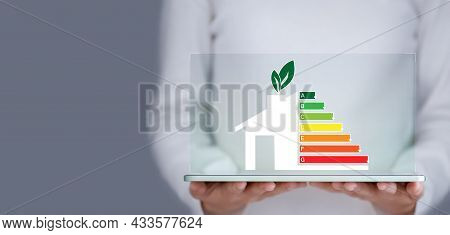 Energy Efficiency And Green Energy Concept, Woman Hand Holding Tablet And Looking At House Efficienc